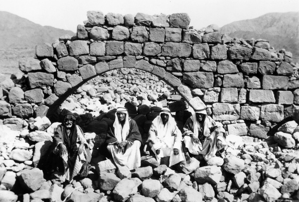 Four local men sit by the ruins of an aqueduct